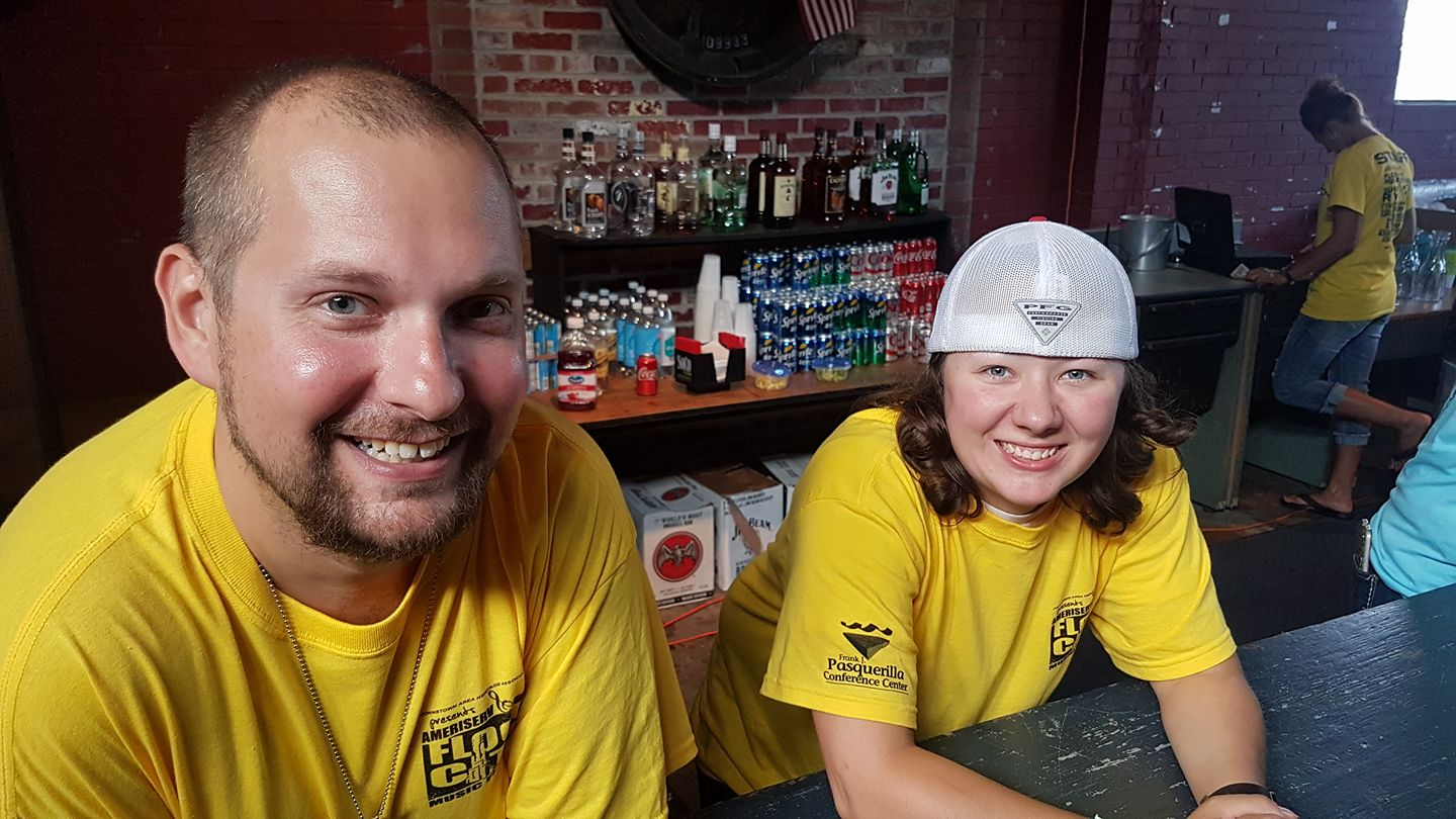 Two bartenders with big smiles await customers at the Flood City Music Festival.